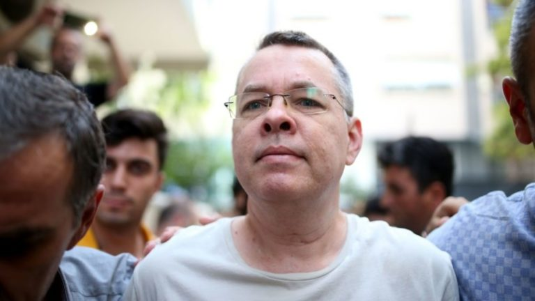 U.S. pastor Andrew Brunson walking with two police officers.