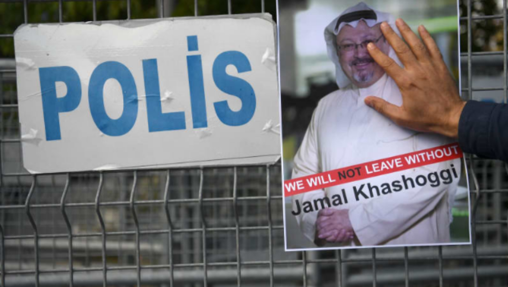 A Jamal Khashoggi poster held by a hand against a police fence.
