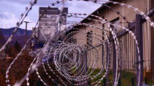Barbed wire around a prison building.